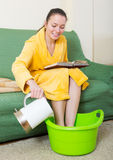 Young blonde taking foot bath Royalty Free Stock Image