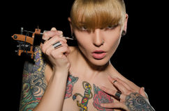 Young blonde with tattoo machine and for them Royalty Free Stock Images