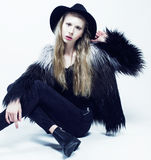 Young blonde teenage girl in hat and fur coat, fashion dressed model, studio shot Stock Photos