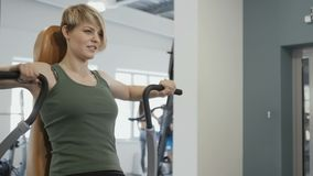 Young blonde training the back on the training apparatus. Young woman wearing sporty outfit is in the gym. Sporty young smiling woman sits at the training stock video footage