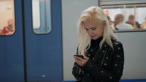 Young blonde travel woman holding a cell phone in her hand waiting on the platform of a railway train. Public transport. Young travel woman holding a cell phone stock footage