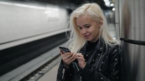 Young blonde travel woman holding a cell phone in her hand waiting on the platform of a railway train. Public transport. Young travel woman holding a cell phone stock video