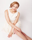Young blonde in white dress posing Royalty Free Stock Photo