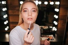 Young blonde woman applying lipgloss on lips. She look on camera. Serious and concentrated. Mirror with light bulbs. Behind royalty free stock image