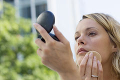 Young blonde woman applying make-up using powder compact, close-up Stock Image