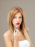 Young blonde woman applying red lipstick brush Royalty Free Stock Photos