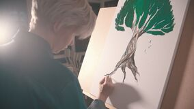 A young blonde woman artist painting a tree root in darker color
