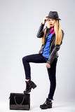 Young blonde woman in autumn casual clothes, black leather jacket, hat, purple scarf and blue shirt, standing with one stock images