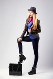 Young blonde woman in autumn casual clothes, black leather jacket, hat, purple scarf and blue shirt, standing with one. Leg on a black bag, wearing boots on a Royalty Free Stock Image