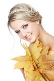 Young blonde woman with autumn leaves in hand Royalty Free Stock Photo