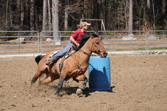 Young blonde woman barrel racing. A young woman turns around a barrel and races to the finish line Stock Photography