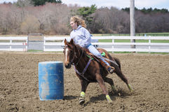 Young blonde woman barrel racing. A young woman turns around a barrel and races to the finish line Royalty Free Stock Photo