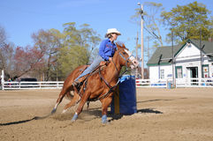 Young blonde woman barrel racing. A young woman turns around a barrel and begins racing to the finish line Stock Photo