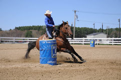 Young blonde woman barrel racing. A young woman turns around a barrel before racing to the finish line Royalty Free Stock Photos