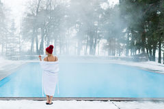 Young blonde woman in bathrobe and red hut near outdoor swimming pool at winter Royalty Free Stock Photos