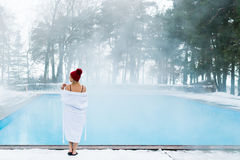 Young blonde woman in bathrobe and red hut near outdoor swimming pool at winter Stock Photo