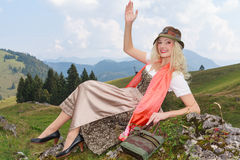 Young blonde woman in Bavarian dirndl smiles and waves. Stock Images