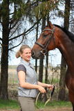 Young blonde woman and bay horse together Royalty Free Stock Photos