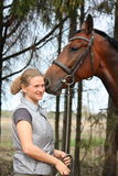 Young blonde woman and bay horse together Royalty Free Stock Photo