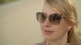 Young blonde woman on the beach taking selfie stock footage