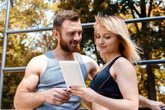 Young blonde woman and bearded man browsing the internet on tabl Stock Photography