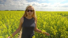 Young blonde woman posing in beautiful rapeseed field stock video