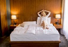 Young blonde woman on the bed looks happy and satisfied. Young blonde woman on the bed in the room looks happy and satisfied Royalty Free Stock Images