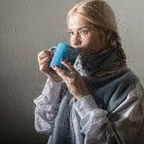 Young blonde woman behind glass with water drops. beautiful girl drinks coffee or tea royalty free stock images
