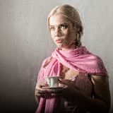Young blonde woman behind glass with water drops. beautiful girl drinks coffee or tea stock photos