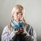 Young blonde woman behind glass with water drops. beautiful girl drinks coffee or tea royalty free stock image