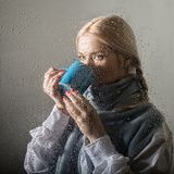 Young blonde woman behind glass with water drops. beautiful girl drinks coffee or tea stock image