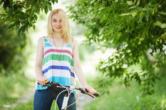 Young blonde woman on a bicycle in the forest Stock Photography