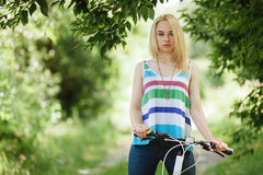 Young blonde woman on a bicycle in the forest Royalty Free Stock Photography