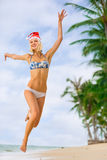 Young blonde woman in bikini and Christmas Santa hat jumping on Royalty Free Stock Photos