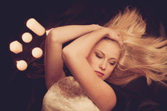 Young blonde woman on black sheets with candels in background Stock Photo