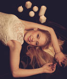 Young blonde woman on black sheets with candels in background Royalty Free Stock Photos