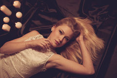 Young blonde woman on black sheets with candels in background Royalty Free Stock Photo