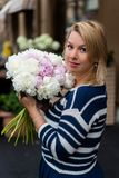 Young blonde woman in blue dress with peonies bouquet Stock Images