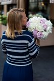 Young blonde woman in blue dress with peonies bouquet stock photos