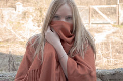 Young blonde woman with blue eyes holding  a poncho between her teeth. Young blonde woman with blue eyes holding  a orange poncho between her teeth Royalty Free Stock Photography