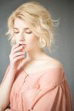 Young blonde woman with blue eyes. Portrait of a beautiful blonde girl. Fashion model. Woman with perfect skin. Woman with white hair in a pink blouse with Stock Image