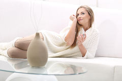 Young blonde woman with bottle of perfume. Young blonde women lying on the sofa. She uses perfume. She smells perfume on your wrist Royalty Free Stock Photography