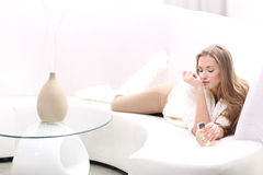 Young blonde woman with bottle of perfume. Young blonde woman lying on the sofa. She smells perfume on your wrist Royalty Free Stock Photos