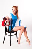 Pretty girl with boxing gloves on chair Royalty Free Stock Photos
