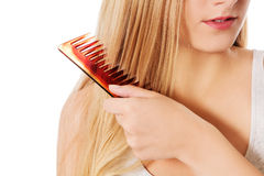 Young blonde woman brushing her hair Royalty Free Stock Photos