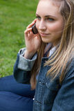 Young blonde woman calling with her mobile phone while sitting i Royalty Free Stock Photos