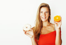 Young blonde woman choosing between donut and apple fruit isolat Stock Photography