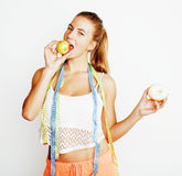 Young blonde woman choosing between donut and apple fruit isolated on white background, lifestyle people concept Stock Photo