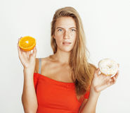 Young blonde woman choosing between donut and orange fruit isolated on white background, lifestyle people concept Royalty Free Stock Photography