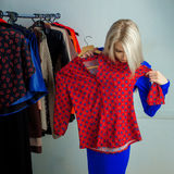 Young blonde woman choosing shirt in clothing store Stock Photos